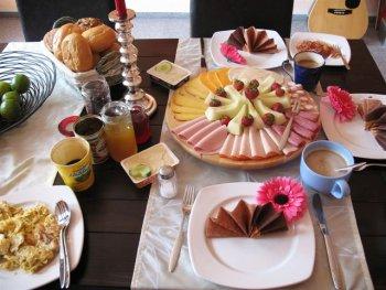 Geburtstags-Frühstückstisch mit Rührei, Speck, Obst und Milchkaffee